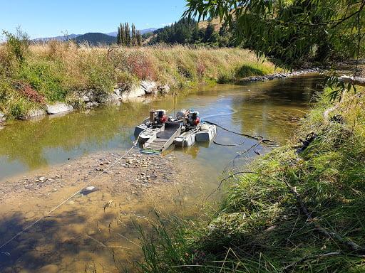 Gold dredge in river bank